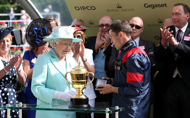 Queen Elizabeth II presents jockey Graham Lee his winner's medal